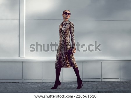 Street fashion concept - pretty elegant woman in leopard dress and sunglasses posing in the city - stock photo