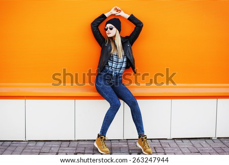 Street fashion concept - stylish cool girl in rock black style posing against a colorful urban wall - stock photo