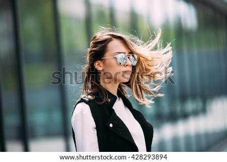 Street fashion concept. Young beautiful model in the city. Beautiful blonde woman wearing sunglasses Hair fluttering in the wind. - stock photo