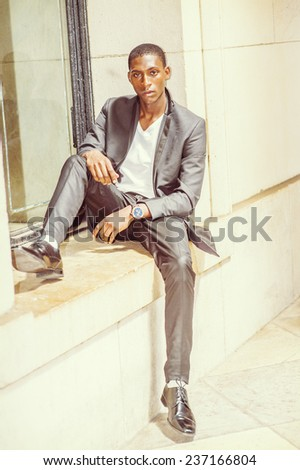 Street Fashion. Dressing in white under wear, fashionable jacket, pants, leather shoes, wearing wristwatch, a young black college student is sitting against a window frame, relaxing, waiting for you.  - stock photo