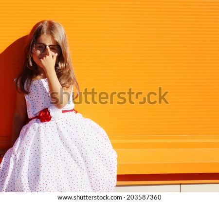 Street fashion little girl in dress near colorful wall - stock photo