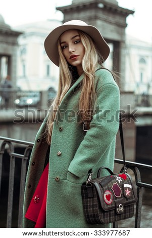Street fashion. Portrait of young beautiful lady in hat with handbag.