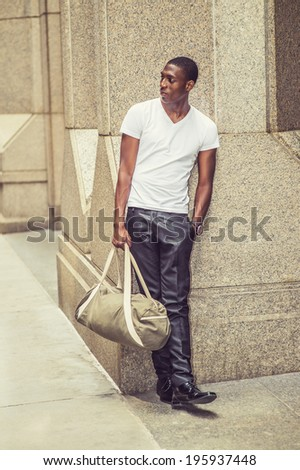 Street Fashion. Wearing a white V neck T shirt, pants, leather shoes, carrying a bag,  a young black college student is standing against a column outside an office building,  looking away.  - stock photo