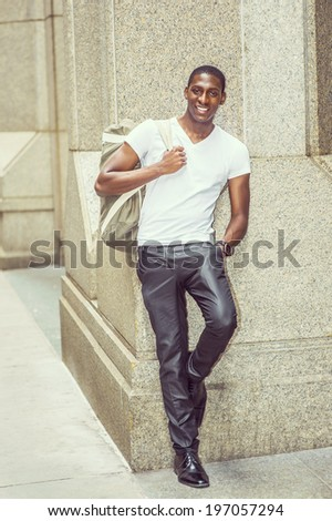 Street Fashion. Wearing a white V neck T shirt, pants, leather shoes, carrying a shoulder bag,  a young black college student is standing against a column outside, smilingly looking at you. - stock photo