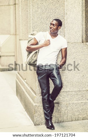 Street Fashion. Wearing a white V neck T shirt, pants, leather shoes, carrying a shoulder bag,  a young black college student is standing against a column outside, smilingly looking away. - stock photo