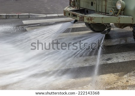 Street flusher in action, equipped with high pressure pumps and specialized flusher heads. Used for street washing, sidewalk and driveway cleaning. Selective focus. - stock photo