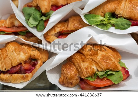 Street food croissants with salmon served in paper bags closeup