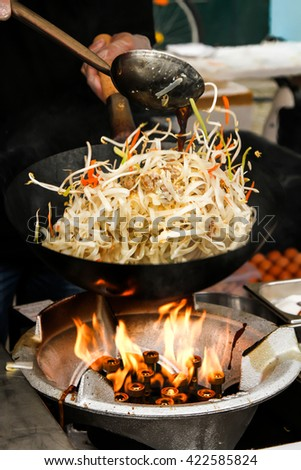 street food. fried noodles in a wok with chicken and shrimp on the open fire, Chinese style - stock photo
