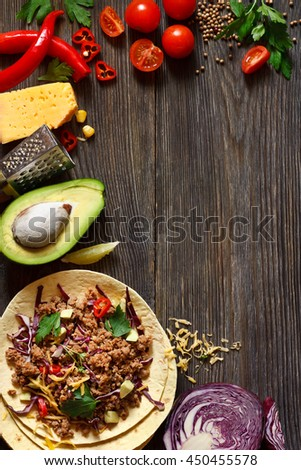 Street food. Mexican tacos and fresh ingredients on wooden board.