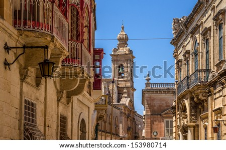 Street in Mdina full of balconies and the Carmelite convent in the end of the street. - stock photo