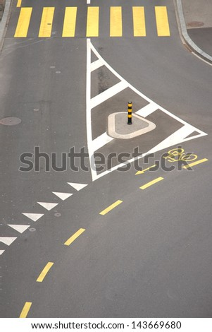 street intersection with yellow zebra crossing and bicycle lane, high angle view - stock photo