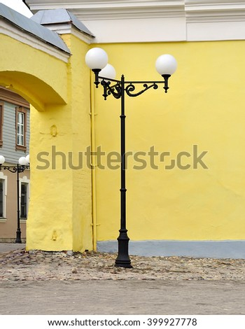 Street lamp against the yellow walls of the old house - stock photo