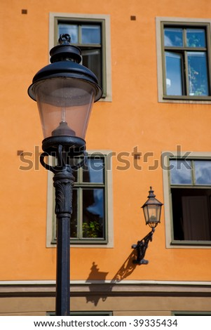 Street lamp and wall lantern of bright orange building with windows in Gamla Stan, Stockholm, Sweden