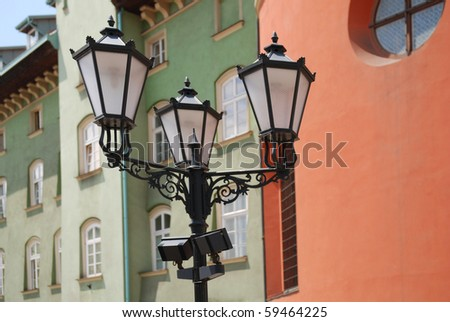 street lamp in front of the wall of green brick
