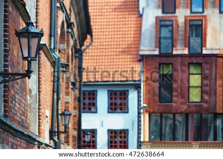 Street lamp on the wall and windows of different shapes in the Old Town Riga