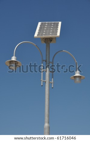 street lamp post with solar panel energy (against blue sky background)