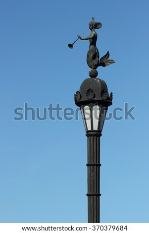 Street lamp sculpture of a mermaid and reedpipe, St. Petersburg, Russia/ Decorative lamp against the blue sky - stock photo