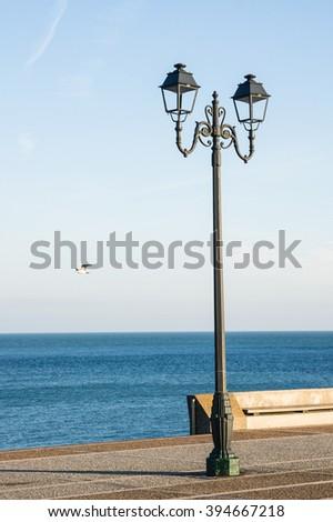 Street lamppost against blue sea background, Etretat, Normandy, France - stock photo