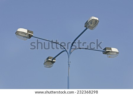 Street Lamppost with four arms on blue sky - stock photo