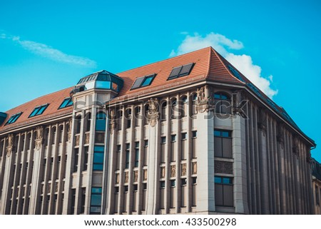 Street level view of classical styled apartments with tiled roof under a clear blue sky - stock photo
