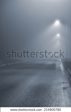 Street lights, foggy misty night, lamp post lanterns, deserted road in mist fog, wet asphalt tarmac, car headlights approaching, vertical, blue key  - stock photo
