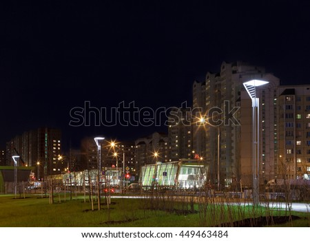 Street lights on boulevard and illuminated subway station. - stock photo