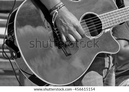 Street Musical Band Play Latin Music. Close-up Of  Guitarist Male Hand And Fingers  Who Touches String On The Black Acoustic Guitar, Black And White Image - stock photo