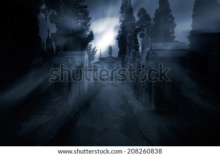 Street of an old european cemetery in a foggy full moon night - stock photo