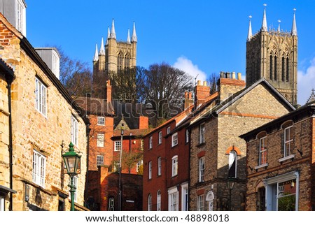 Street of historic houses in downtown Lincoln, England overlooked by the ancient Medieval cathedral. - stock photo