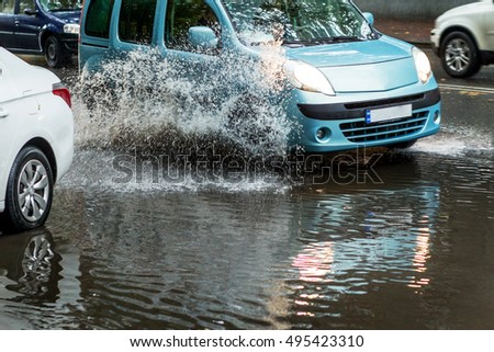Street of the city flooded after heavy rains. Large puddles in the streets after the rain. Bright background splashes from under the wheels of the cars driving on the puddles. Strong motion blur
