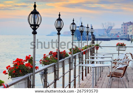 Street open cafe with view at the canal, Venice, Italy. Tables and seats are empty. Flowers decorate cafe. Cozy romantic evening place. - stock photo