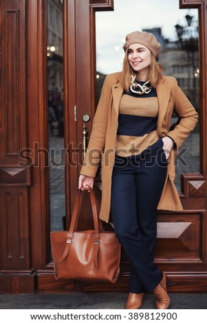 Street photo of young beautiful happy smiling lady wearing stylish classic clothes. Model looking aside. Full body portrait. Female fashion concept. City lifestyle.  - stock photo