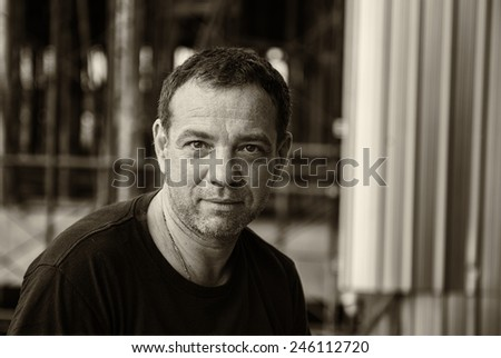 Street photography of smiling 40-year-old man. Sepia toned - stock photo