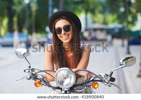 Street portrait of pretty smiling girl on motorbike. Fashion young woman wearing sunglasses and stylish hat on a retro scooter on a summer day in a cityspace. - stock photo