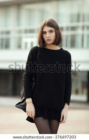 Street portrait of young elegant brunette hipster woman in black blouse and skirt against a blurred city background