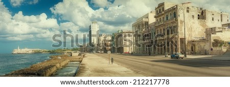 Street scene in Old Havana with old decaying buildings at Malecon and the El Morro castle - stock photo