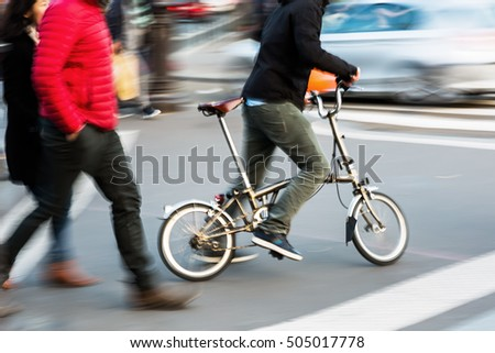 street scene with a man with a city bicycle crossing a street, picture was made in motion blur