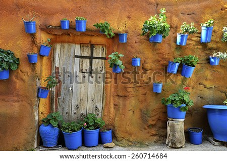 Street scene with pots of flower in the wall - stock photo