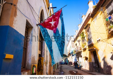 Street  sidelined by decaying buildings in Old Havana with a big cuban flag - stock photo