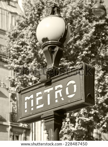 Street sign at the entrance to the Paris Metro, banner with text on the street lamp, retro stylized sepia toned photo