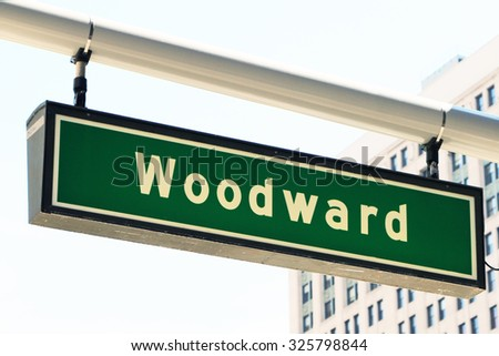 """Street sign for Woodward Avenue, a main thoroughfare in the City of Detroit, Michigan.  This is where the annual """"Dream Cruise"""" is held.  There is a generic office building in the background. - stock photo"""