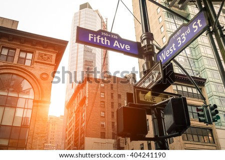 Street sign of Fifth Ave and West 33rd St at sunset in New York City - Urban concept and road direction in Manhattan downtown - American world famous capital destination on warm dramatic filtered look - stock photo