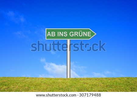 Street Sign showing nature trip in front of blue sky on green grass