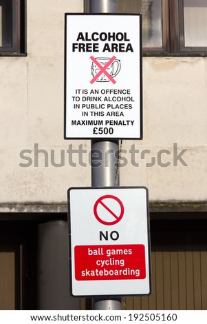 Street sign warning that the area is a no alcohol zone to prevent drunken behaviour. Below is a no ball games, cycling, skateboarding sign - stock photo