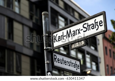 Street signs in an intersection says it is Larl-Marx Strasse and Reuterstrasse in Berlin, Germany.