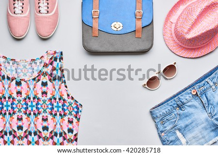Street style Fashion dirl clothes accessories set. Hipster woman, trendy handbag, top, denim, gumshoes, pink hat and sunglasses. Bright urban creative outfit. Overhead, top view on gray background
