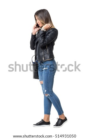 Street style fashion girl walking while talking on the phone and adjusting hair. Full body length portrait isolated over white background