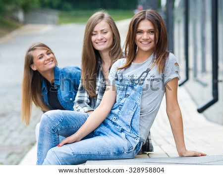 Street style girl. Portrait of young and beautiful girl standing on the street. Her friends are behind her, having fun and good cheerful time - stock photo