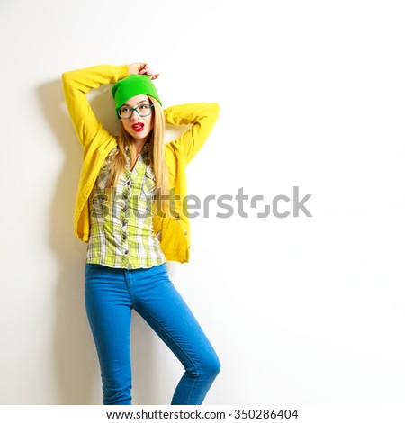 Street Style Hipster Girl with Hands behind Head Posing at White Background. Not Isolated Photo with Shadow. Trendy Casual Fashion Outfit. Copy Space.