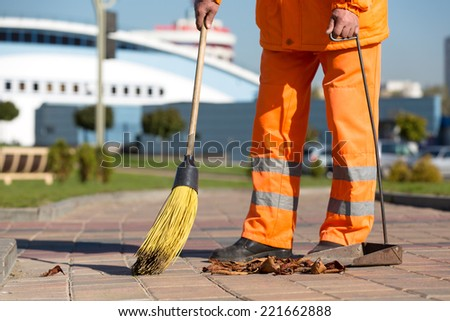 Street Sweeper cleaning city sidewalk with broom tool and dustpan
